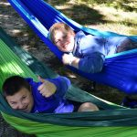 Two boys both laying in hammocks